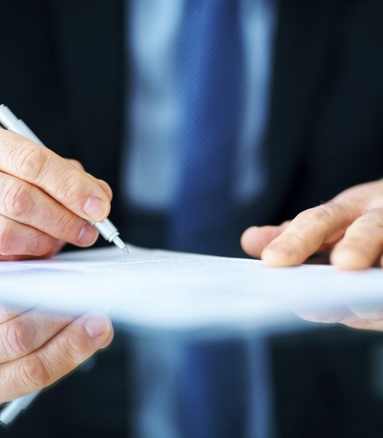 Business man hands signing document