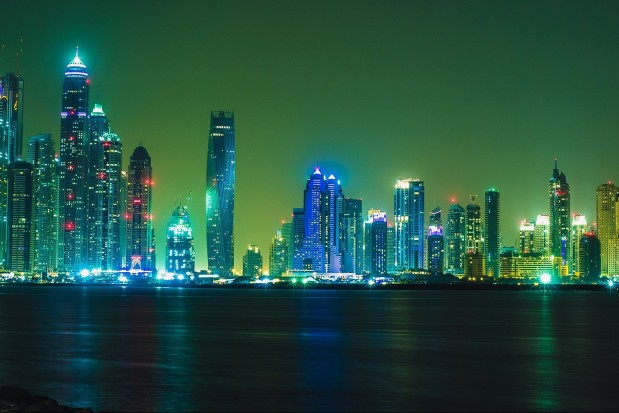 Extremely Wide Panorama of Dubai Skyline in Night with vibrant colors with reflection over Arabian Sea.